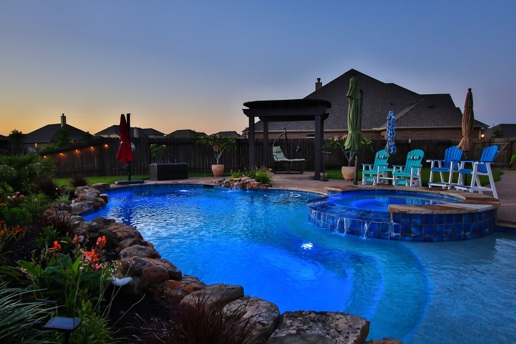 Custom Lit Freeform Pool at Night with Raised Spa & Rock Waterfall