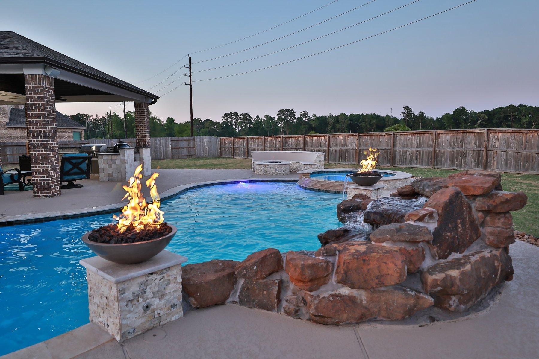 Freeform Pool with Rock Waterfall, Custom Lighting and Fire Bowls