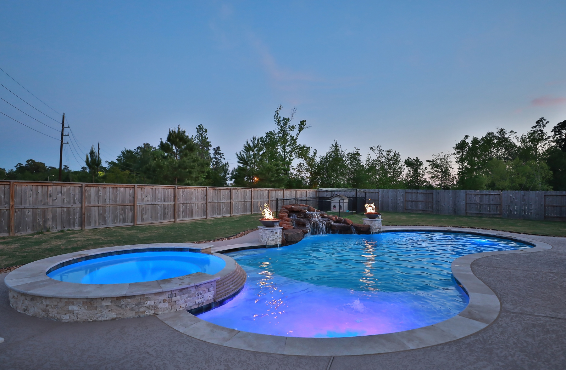 Freeform Pool with Rock Waterfall, Tanning Ledge, Custom Lighting and Fire Bowls