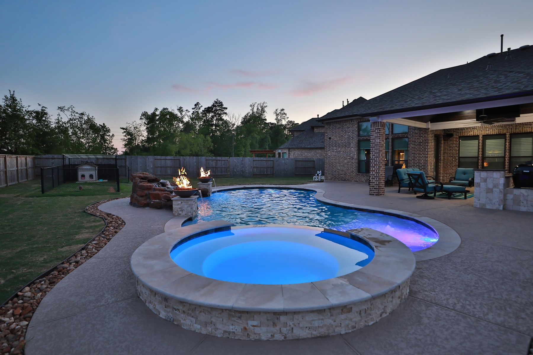 Spa View of Freeform Pool with Rock Waterfall, Custom Lighting and Fire Bowls