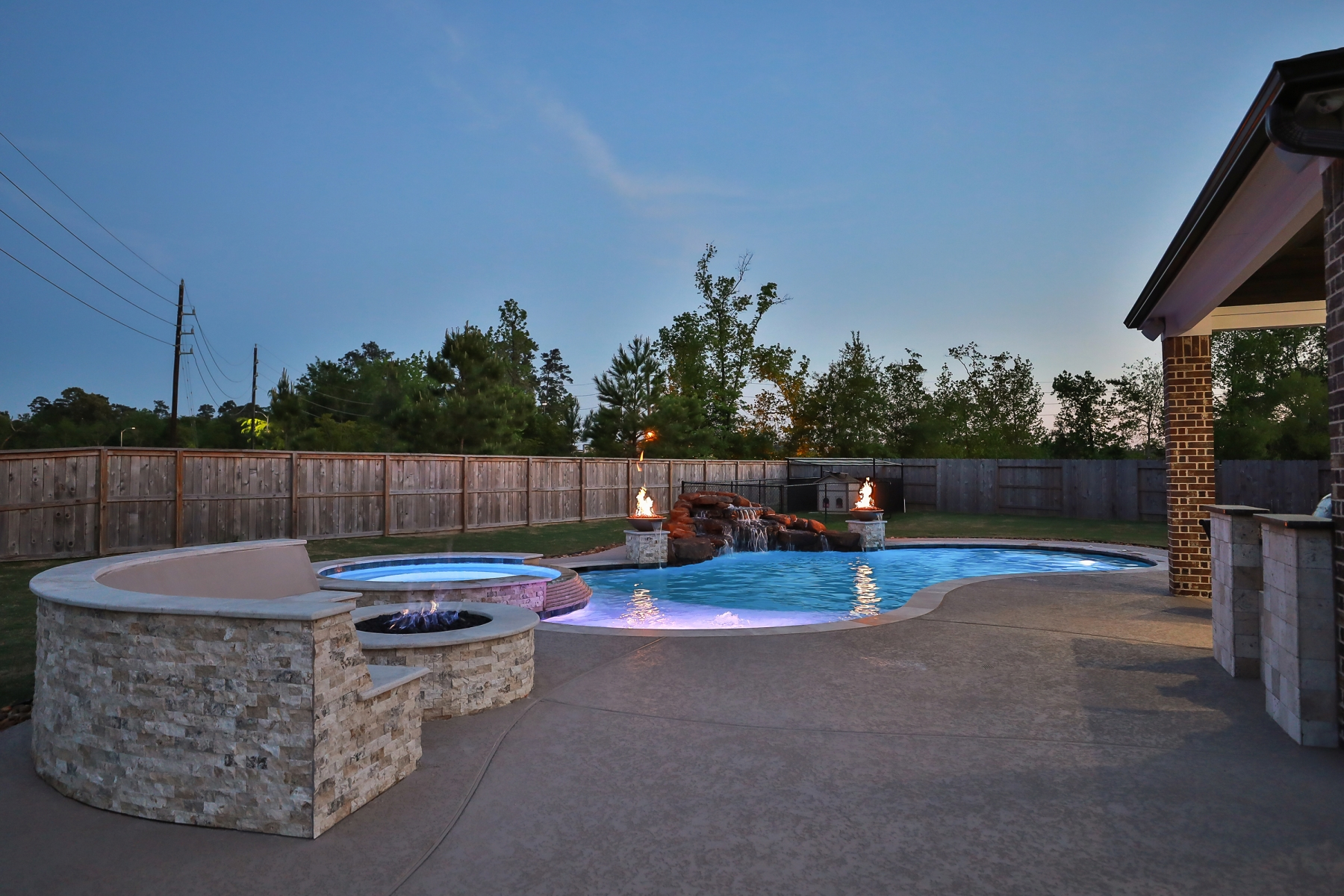 View From Fire Pit Seating Area of Freeform Pool with Rock Waterfall, Custom Lighting and Fire Bowls