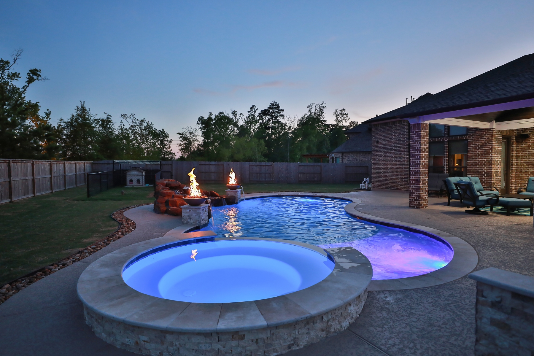 Spa View at Night - Freeform Pool with Rock Waterfall, Custom Lighting and Fire Bowls