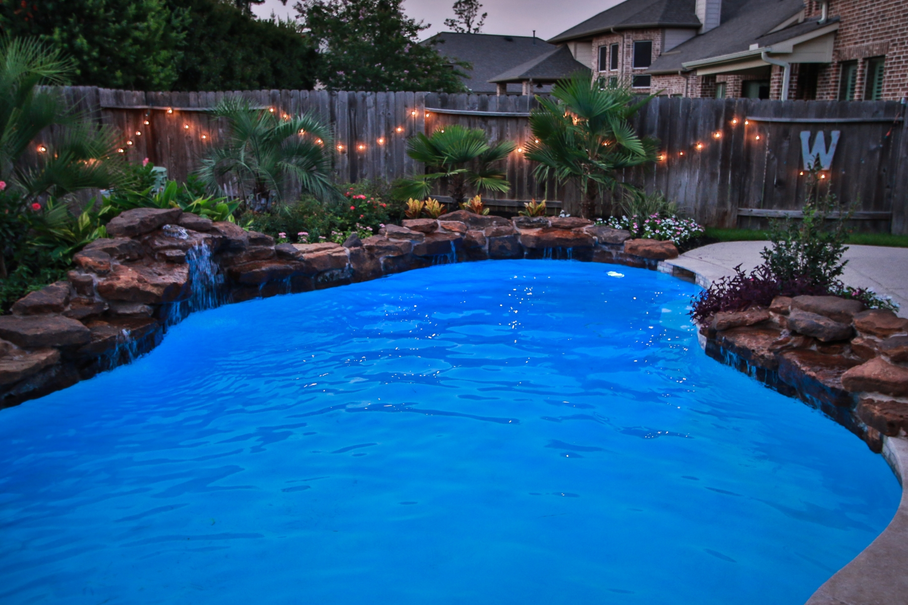 Freeform Pool with Rock Waterfall and Custom Lighting at Night