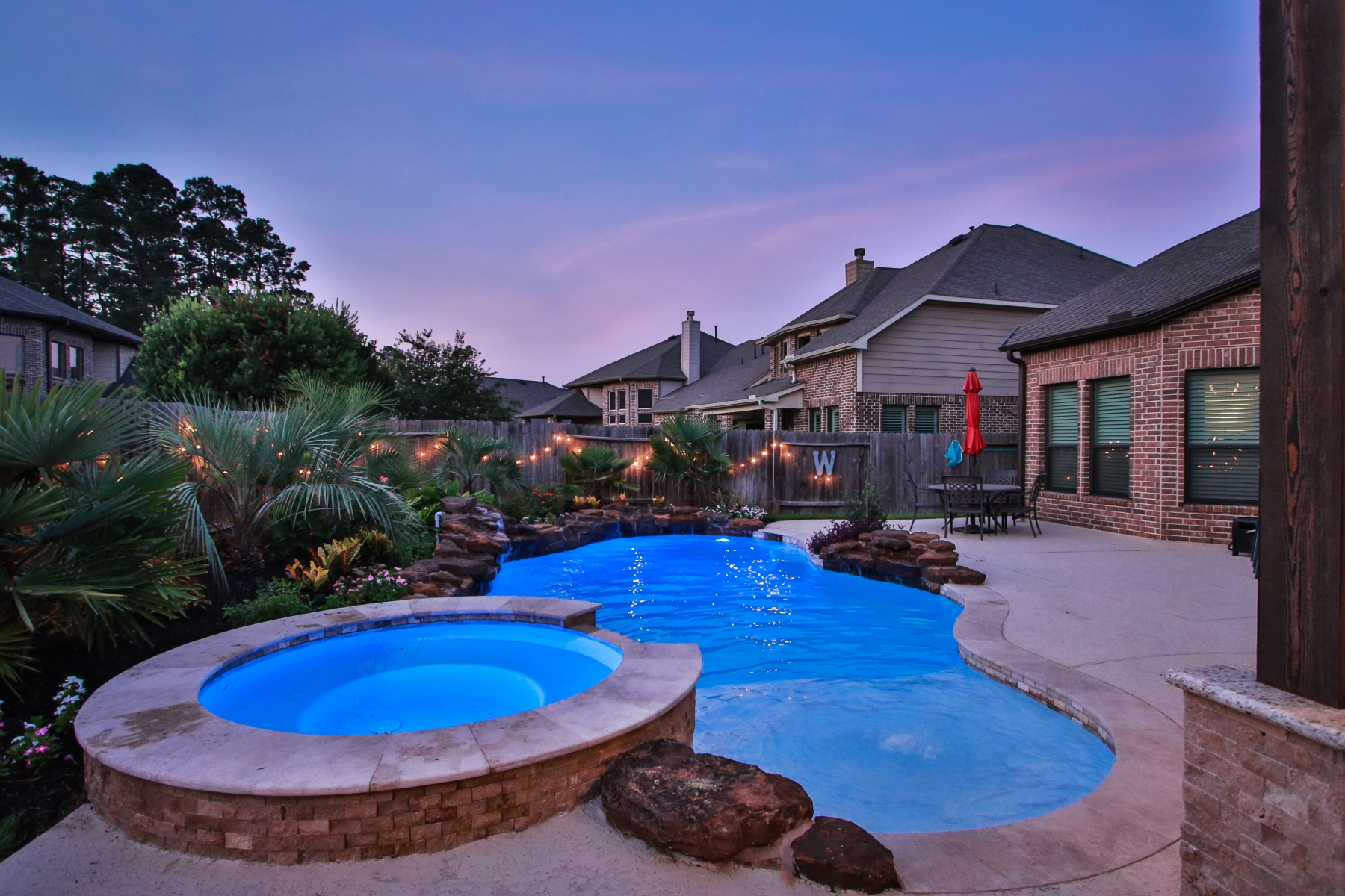 Freeform Pool with Raised Spa, Rock Waterfall, Custom Lighting at Night