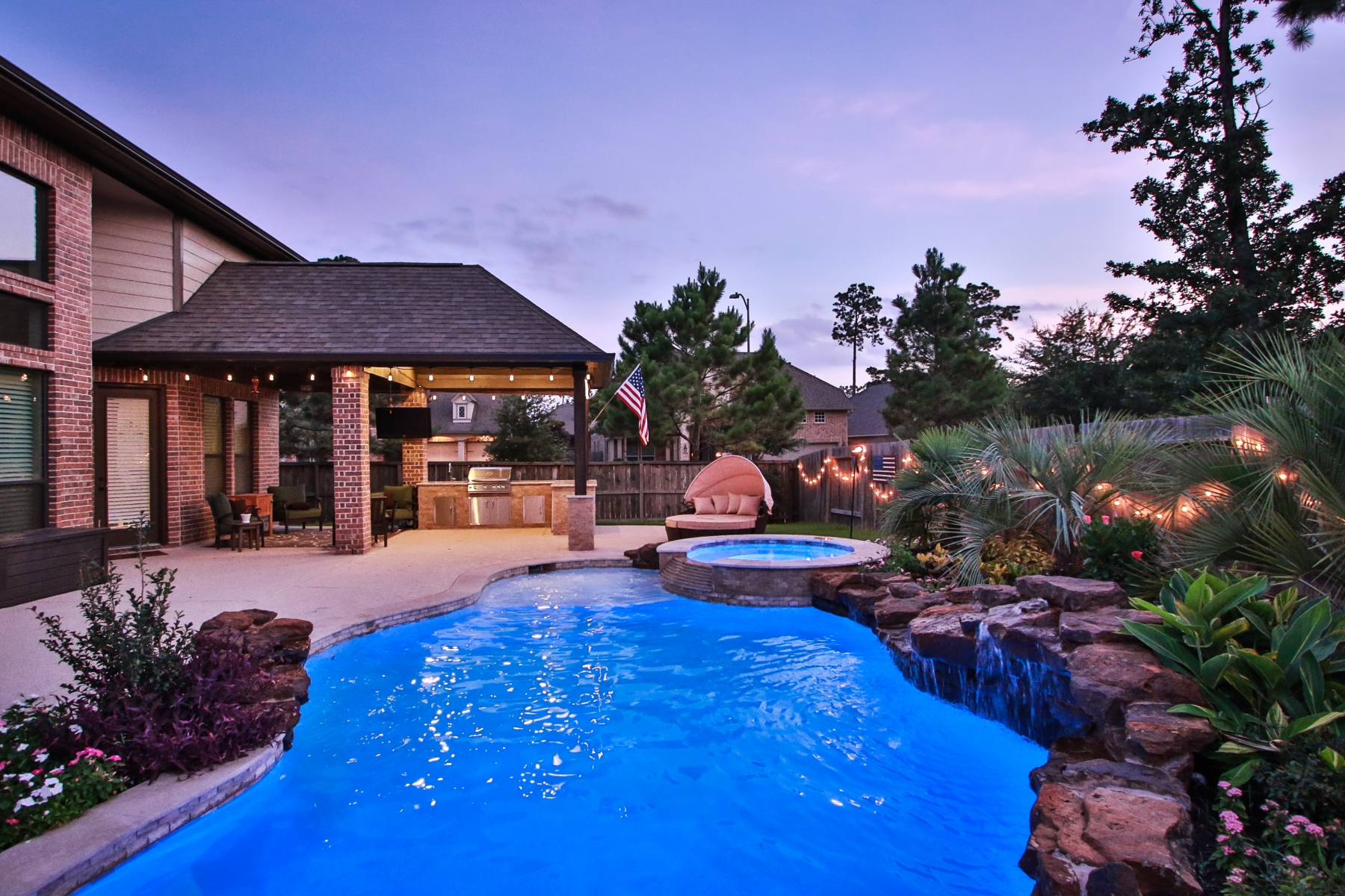 Pool View of Freeform Pool, Spa, Waterfall and Covered Patio with Outdoor Kitchen