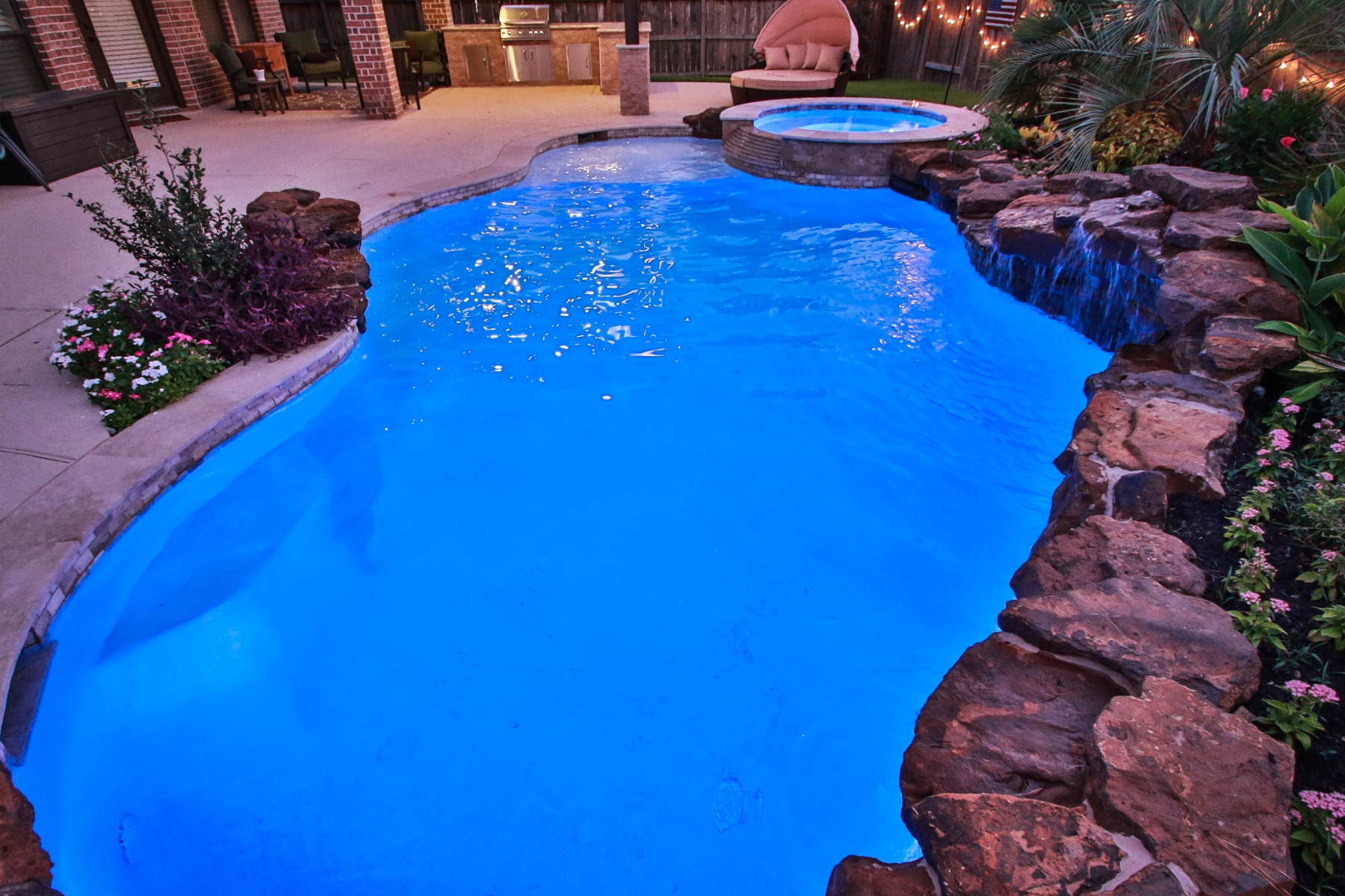 Freeform Pool at Night with Custom Lighting, Spa & Waterfall