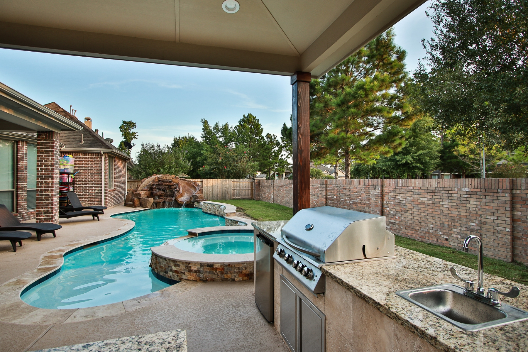 Freeform Pool Viewed From Outdoor Kitchen and Covered Patio