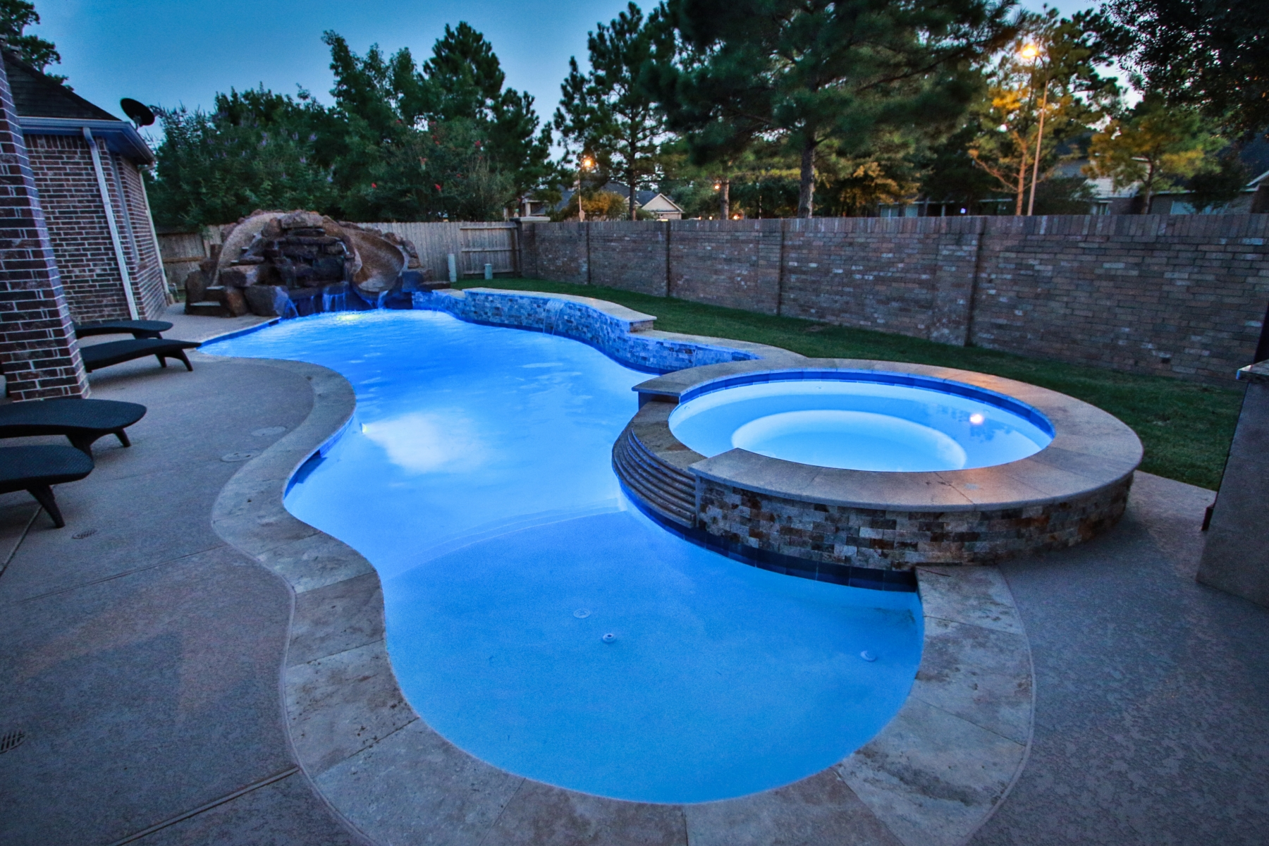 Freeform Pool at Night withTanning Ledge, Raised Spa and Rock Water Slide