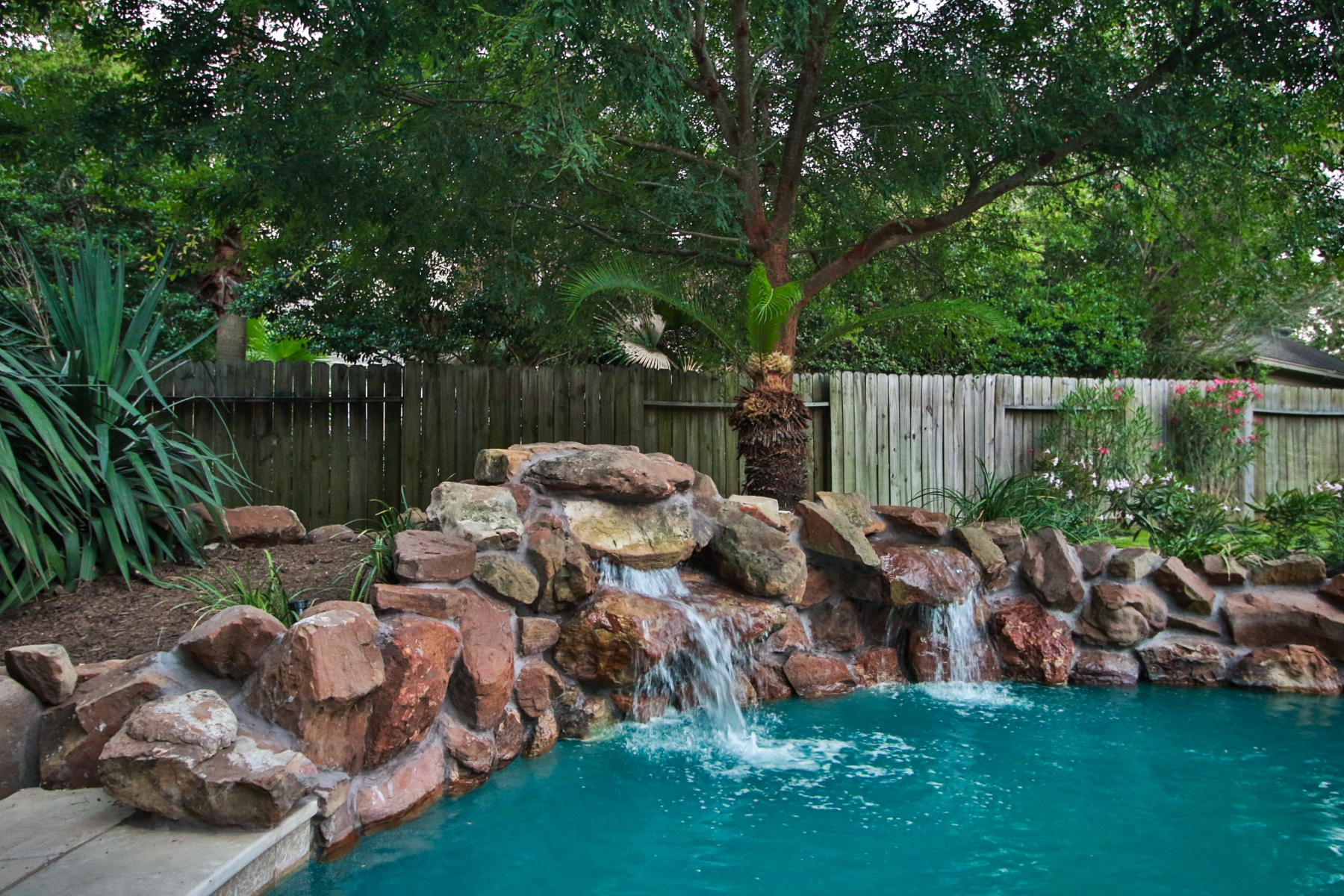 Freeform Pool With Custom Lighting & Rock Water Fall