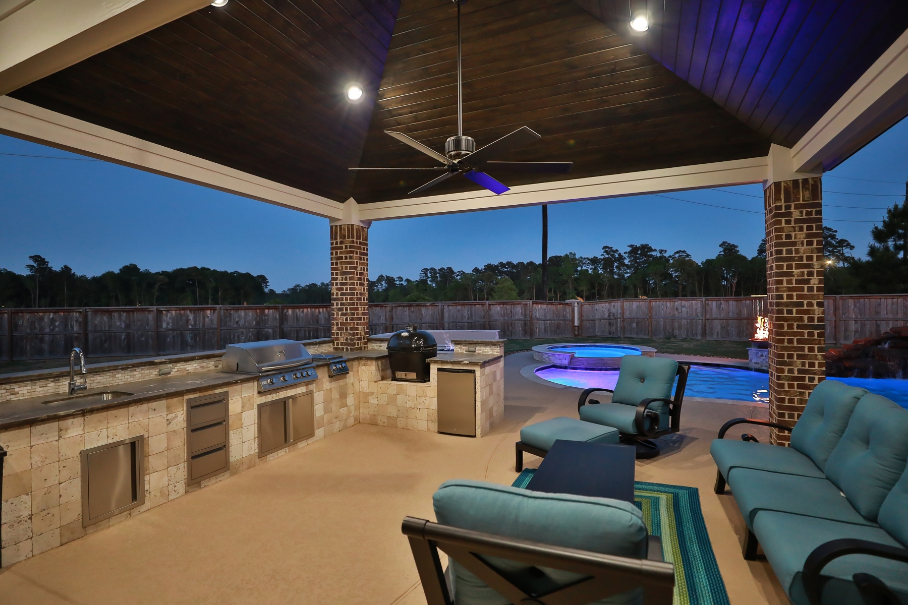 Outdoor Kitchen and Living Area Overlooking Pool at Night
